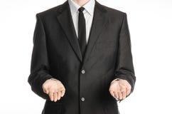 Affärsman och gestämne: en man i en svart dräkt och band som rymmer två främst för händer isolerat på vit bakgrund i studio Arkivfoton