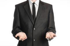 Affärsman och gestämne: en man i en svart dräkt och band som rymmer två främst för händer isolerat på vit bakgrund i studio Royaltyfri Bild