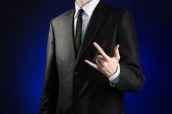 Affärsman och gestämne: en man i en svart dräkt- och vitskjorta visar att ett handtecken vaggar på ett mörker - blå bakgrund i st Arkivbilder