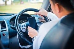 Affärsman- och hålltelefon i bil arkivfoto