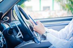 Affärsman- och hålltelefon i bil royaltyfri bild