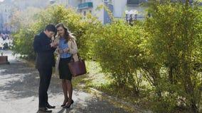Affärsman och kvinna som har det utomhus- mötet och konversation arkivfilmer