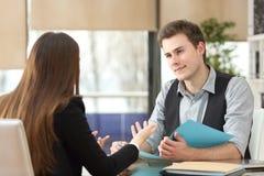 Affärsman och kvinna som har en intervju på kontoret royaltyfria bilder