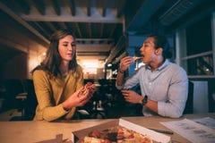 Affärsman och kvinna som sent äter pizza i natten på kontoret arkivbilder