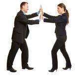 Affärsman och kvinna som skjuter händer arkivfoto