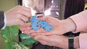 Affärsman- och kvinnahänder som utbyter pusselstycken på affärskontoret fotografering för bildbyråer