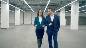 Affärsman och kvinnlig fastighetsmäklare att diskutera ett projekt, medan gå stock video