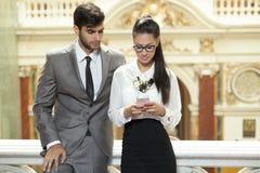 Affärsman och meddelande för text för affärskvinna läs- Royaltyfri Fotografi