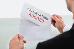 Affärsman Opening Audit Letter i regeringsställning arkivbilder