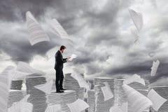 Affärsman på arbete över en hög av pappers- torn av arbetssedlar arkivbild