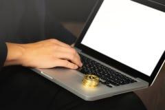 Affärsman på bärbara datorn med bitcoinmynt royaltyfri foto