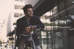 Affärsman på cykeln som kontrollerar tid royaltyfri foto