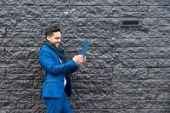 Affärsman på den blåa dräkten som tar bilden med minnestavlan royaltyfri fotografi