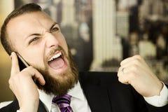 Affärsman på den känsliga framgången för telefon royaltyfri foto