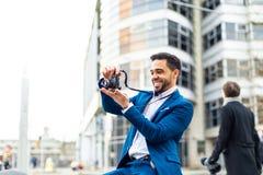 Affärsman på dräkten som utomhus tar en bild arkivfoton