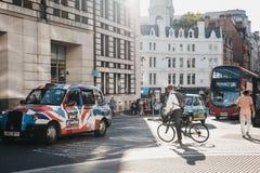 Affärsman på en väntande på trafik för cykel som på passerar en gata fotografering för bildbyråer