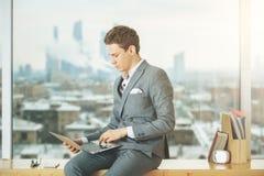 Affärsman på fönsterbräda genom att använda bärbara datorn royaltyfri bild