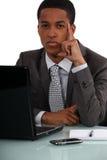 Affärsman på hans tänka för skrivbord arkivbild