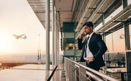 Affärsman på påringning för danande för flygplatsvardagsrumbalkong royaltyfri foto
