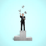 Affärsman på podiet som kastar och fångar pengarsymboler Arkivbild