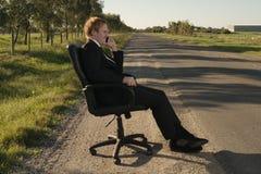 Affärsman på sidovägen i stol Arkivbilder