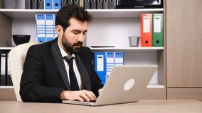 Affärsman på skriva för skrivbord som är ilsket ett svar till en email lager videofilmer