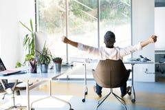Affärsman på skrivbordet i hans kontor som sträcker armar Arkivfoto