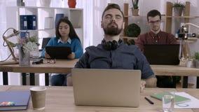 Affärsman på skrivbordet som i regeringsställning sträcker armar lager videofilmer
