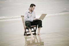 Affärsman på stranden med bärbar dator Royaltyfri Foto