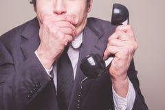 Affärsman på telefonen som täcker hans mun Arkivfoto