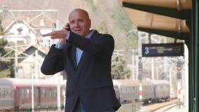 Affärsman In Railway Station med mobiltelefonen i passagerare för drev för handhonnör royaltyfria foton
