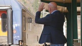 Affärsman In Railway Station med mobiltelefonen i passagerare för drev för handhonnör royaltyfri bild