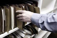 Affärsman Reaching Hand för mappar på hylla Arkivbild