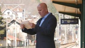 Affärsman Read Newspaper Waiting ett drev i järnvägsstation royaltyfri fotografi