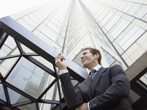 Affärsman Reading SMS på mobiltelefonen mot kontorsbyggnad Royaltyfri Bild