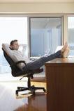 Affärsman Reclining With Feet upp på skrivbordet Fotografering för Bildbyråer