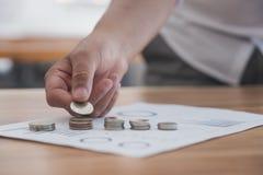Affärsman satta mynt på pengarbunt affärsfinans och inves Royaltyfri Fotografi