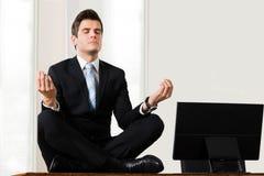 Affärsman Sitting In Lotus Position At Desk Arkivbild