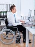 Affärsman Sitting On Wheelchair och användadator Arkivbild