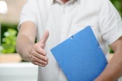 Affärsman som är klar till handskakningen som i regeringsställning står Arkivfoto