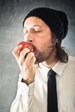 Affärsman som äter det röda äpplet fotografering för bildbyråer