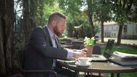 Affärsman som äter lunch under arbete steadicamskott stock video