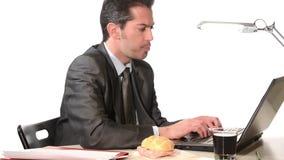 Affärsman som äter sjuklig mat stock video