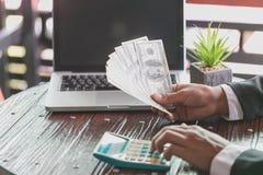 Affärsman som över visar en spridning av kassa och att spendera pengar eller vinst från begrepp för affärsoperationer arkivfoton