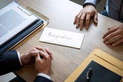 Affärsman som överför ett avsägelsebrev till arbetsgivareframstickandet i ord royaltyfria bilder