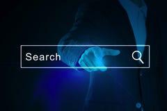 Affärsman som aktiverar en tom sökandestång eller navigeringstången på en faktisk manöverenhet, eller skärm med hans finger Arkivbild