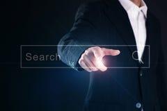Affärsman som aktiverar en tom sökandestång eller navigeringstången på en faktisk manöverenhet, eller skärm med hans finger Arkivfoto