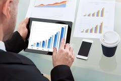 Affärsman som analyserar en graf på en minnestavla Fotografering för Bildbyråer