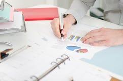 Affärsman som analyserar grafer Arkivbild