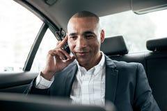 Affärsman som använder bärbar datorsammanträde i bil arkivfoton